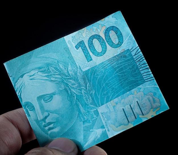 Un uomo in possesso di una banconota da 100 dollari brasiliani che è il real brasiliano su sfondo nero