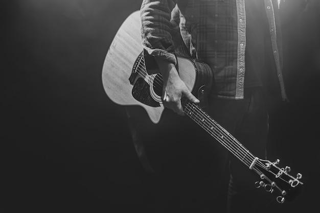 Un uomo che tiene una chitarra acustica nelle sue mani copia spazio.
