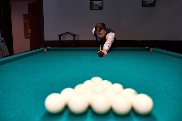 Uomo che tiene il braccio sul tavolo da biliardo, gioca a biliardo o si prepara a sparare palle da biliardo biliardo sport gioco snooker