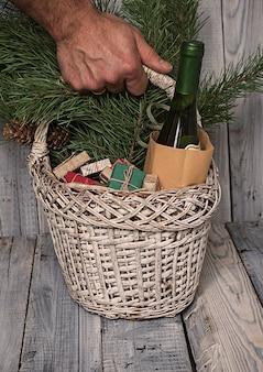 Uomo che tiene un cesto con regali di natale, rami di pino e una bottiglia di vino