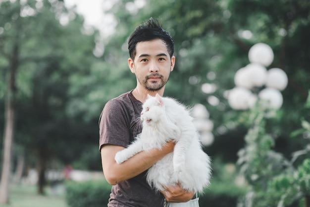 Uomo che tiene un bellissimo gatto persiano peloso nel parco
