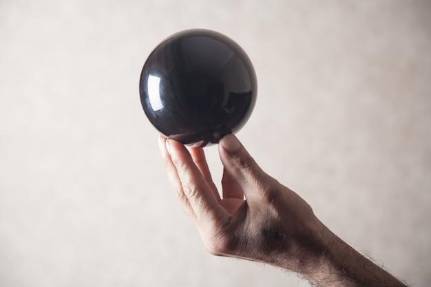 Uomo che tiene la sfera di cristallo nera.