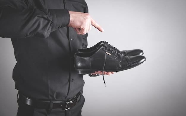 Uomo che tiene le scarpe nere. concetto di moda