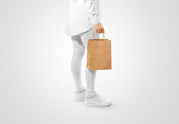 Uomo che tiene il sacchetto di carta marrone in bianco del mestiere