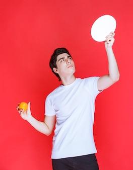 Uomo che tiene un'etichetta vuota e che promuove un frutto arancione.