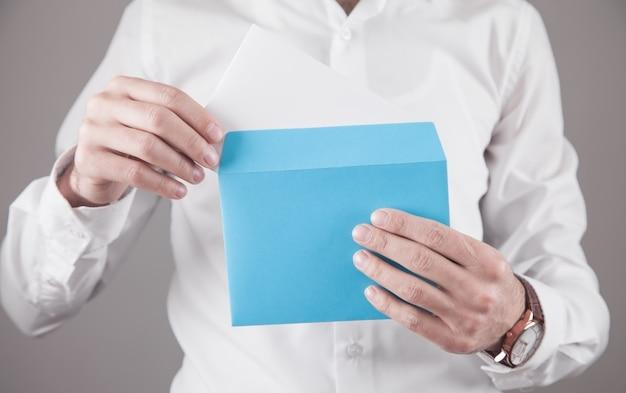Uomo che tiene la busta blu della posta.