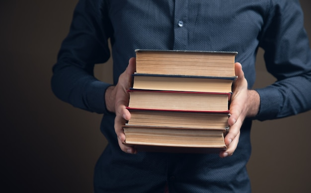 Uomo con libri in mano su superficie marrone