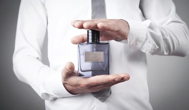 Uomo che tiene una bottiglia di profumo.