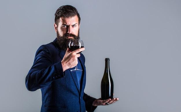 Uomo che tiene la bottiglia con champagne, vino. bottiglia, bicchiere di vino rosso.