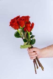 Uomo che tiene un mazzo di bellissime rose rosse su sfondo bianco. san valentino.