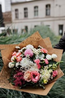 Uomo con in mano un mazzo di fiori colorati