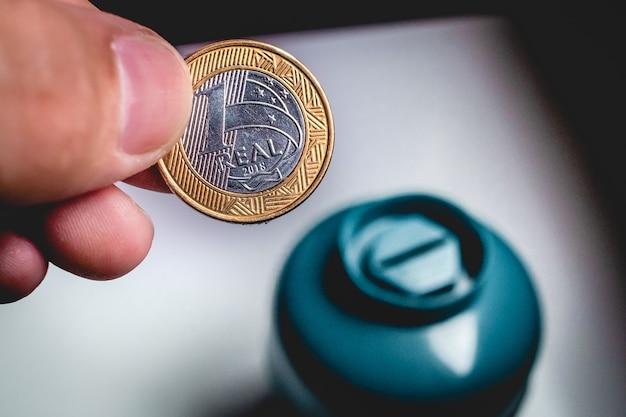 Un uomo che tiene una moneta brasiliana per risparmiare denaro nella scatola del centesimo