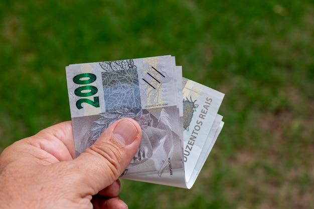 Uomo che tiene bollette di denaro brasiliane con sfondo verde sfocato.