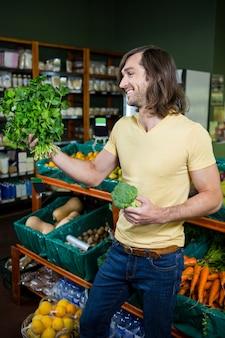 Equipaggi il mazzo della tenuta di erbe e di broccoli nella sezione organica
