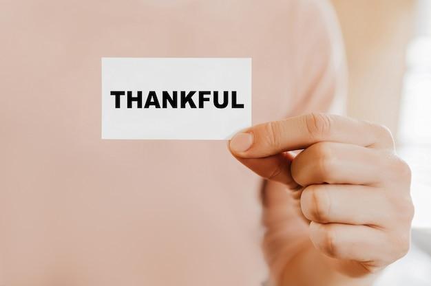 Uomo con in mano un biglietto da visita con thankful