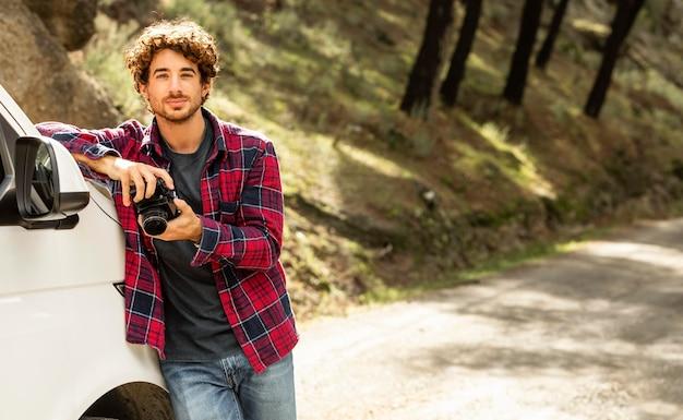 Uomo che tiene la macchina fotografica e che si appoggia sulla macchina durante un viaggio su strada