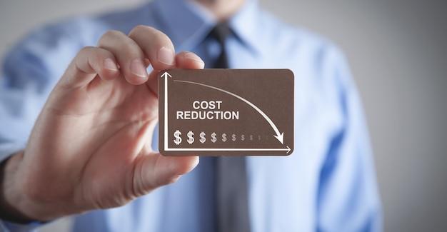 Uomo che tiene la carta di cartone. riduzione dei costi. simboli del dollaro e freccia giù. attività commerciale. finanza