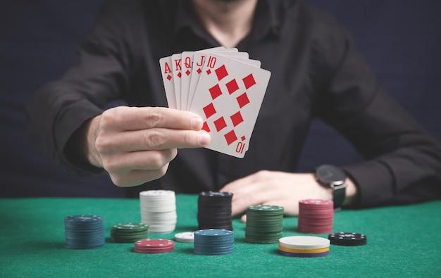Uomo che tiene le carte con fiches del casinò sul tavolo verde.