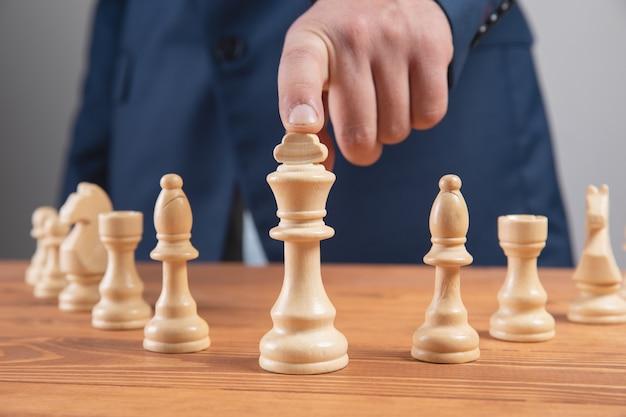Uomo che tiene un pezzo degli scacchi