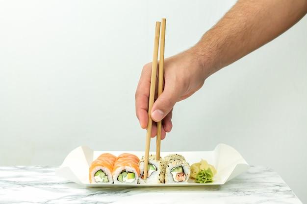 Uomo che tiene le bacchette e mangia sushi giapponese impostato a casa.