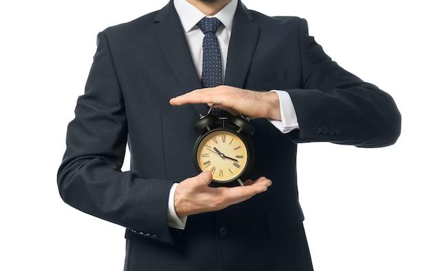 Uomo che tiene orologio su bianco.