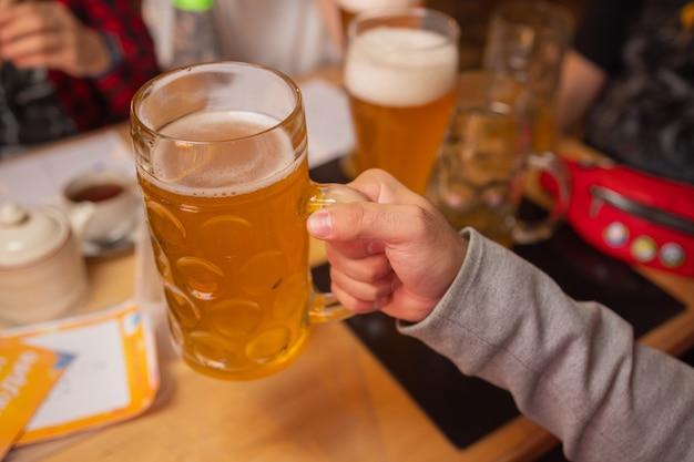 Man holding cold beer glass con la sua mano. birra lager fredda rinfrescante.