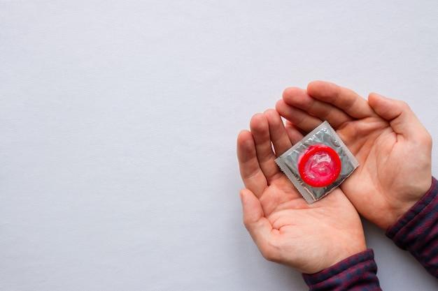 Uomo che tiene i preservativi colorati