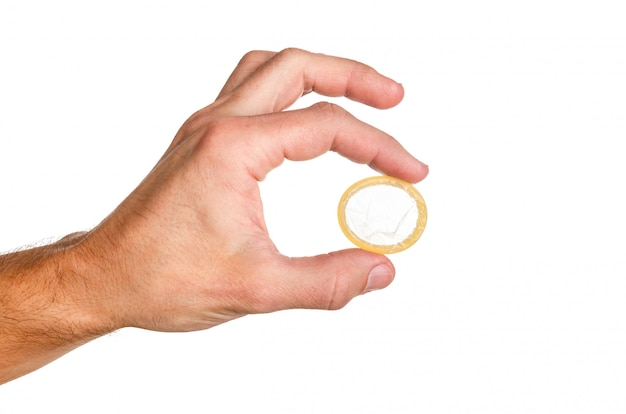Uomo che tiene un preservativo con due dita