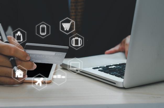 Uomo in possesso di una carta di credito per pagare beni o servizi online o fare acquisti online. concetto di affari finanziari icona schermo virtuale