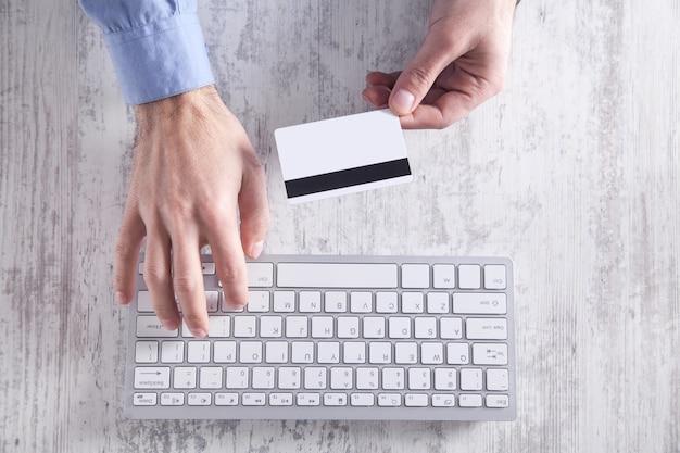 Uomo che tiene la carta di credito e digitando sulla tastiera. pagamento e acquisti online