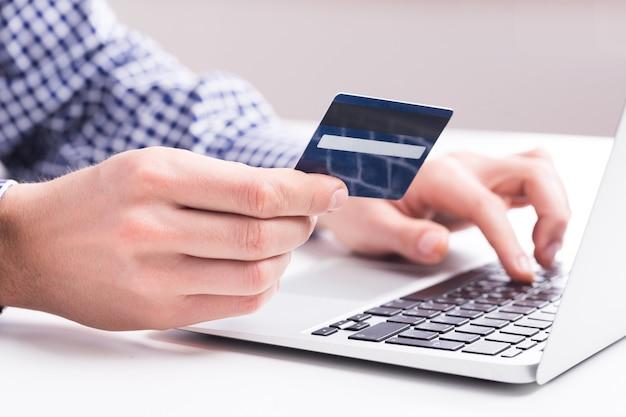 Uomo in possesso di una carta di credito e digitando. acquisti online su internet utilizzando un laptop