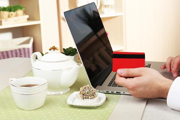 Uomo che tiene la carta di credito e lavora al computer portatile su sfondo interno domestico