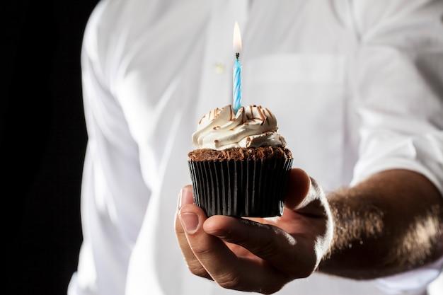 Un uomo che tiene un cupcake con una candela in un gesto di donazione.