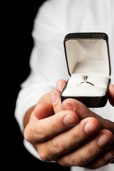 Un uomo che tiene un anello di diamanti in un gesto di donazione.