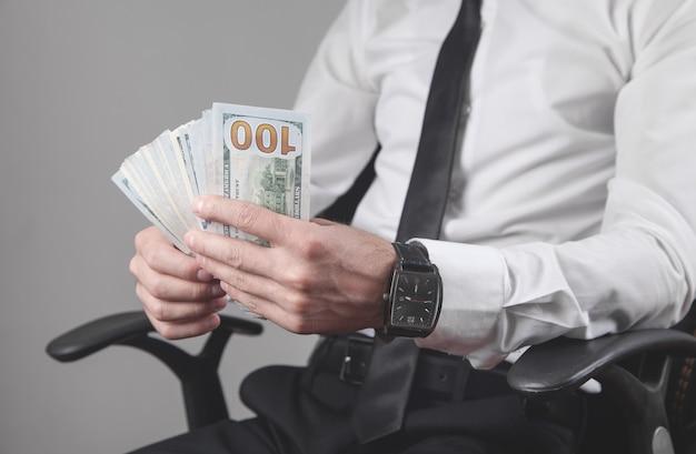 Uomo che tiene i dollari in ufficio.