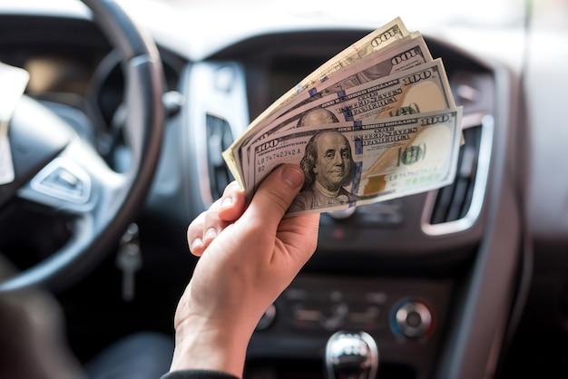Uomo che tiene i dollari che si siedono nell'acquisto o nell'affitto di automobile corrompono