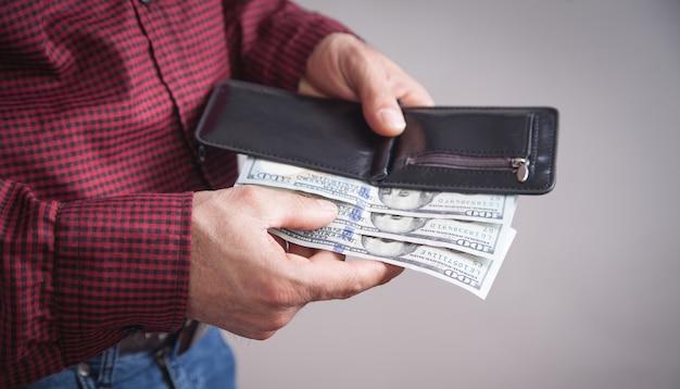 Uomo che tiene i dollari con il portafoglio in piedi su grigio.