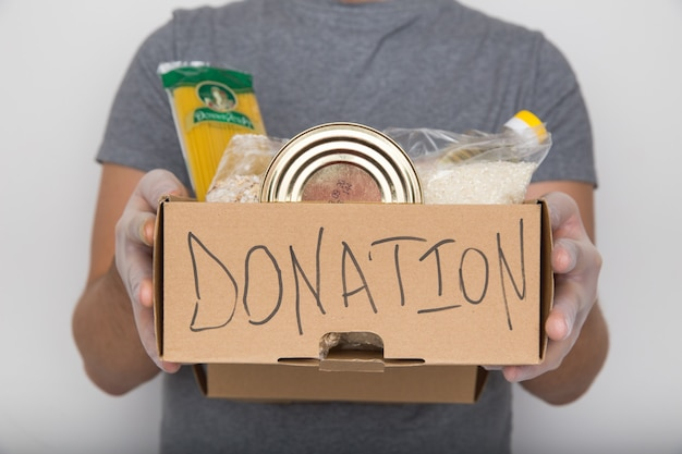 Un uomo che tiene una scatola di donazione di prodotti diversi