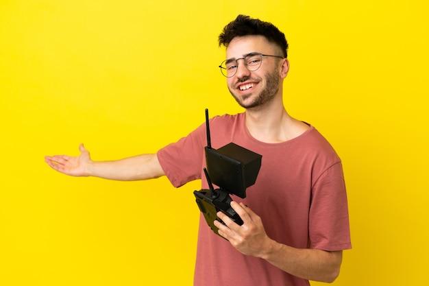 Uomo con in mano un telecomando drone isolato su sfondo giallo che estende le mani di lato per invitare a venire