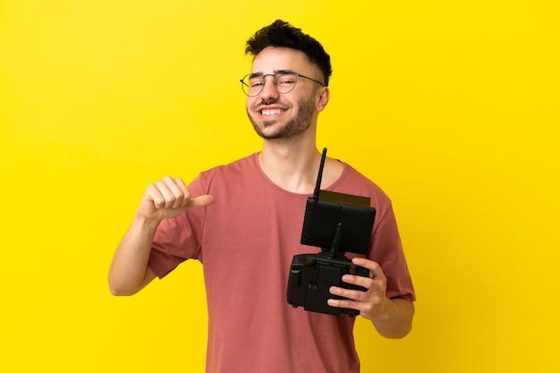 Uomo con in mano un telecomando drone isolato su sfondo giallo orgoglioso e soddisfatto di sé