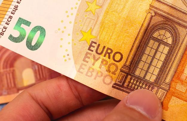 Un uomo con una banconota da cinquanta euro fifty