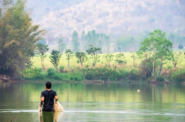 Uomo che tiene le reti da pesca a piedi in acqua sfondo sfocato montagne e alberi