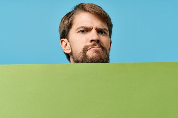 Uomo che tiene davanti a lui e banner verde copy space ritagliata vista marketing modulo isolato