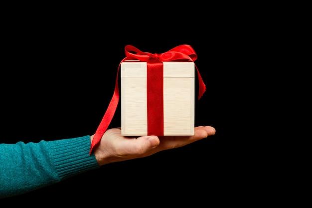 Un uomo che tiene un regalo su uno sfondo nero