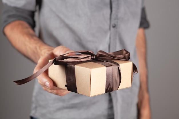 Un uomo che tiene in mano una confezione regalo. su sfondo grigio
