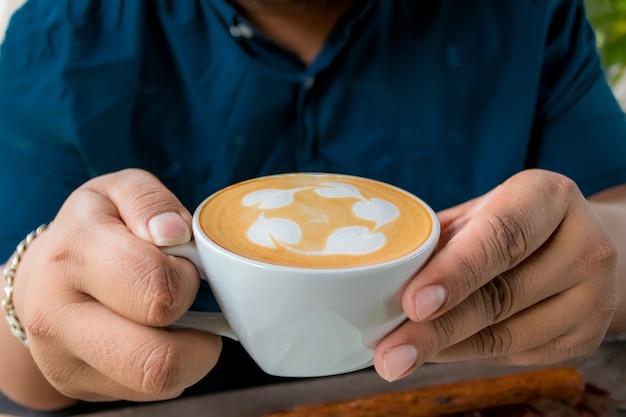Un uomo che tiene un bicchiere di latte caffè in mano su un tavolo di legno