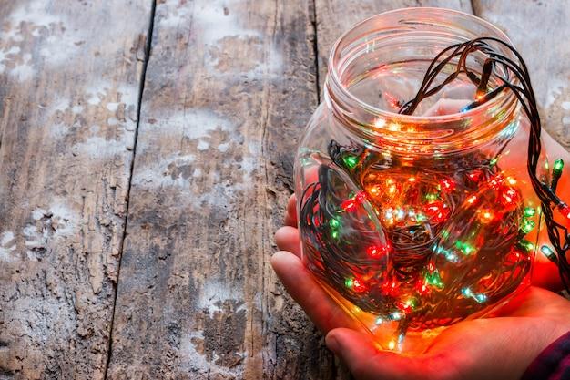 Equipaggi la tenuta del barattolo di vetro con una ghirlanda su un fondo di legno