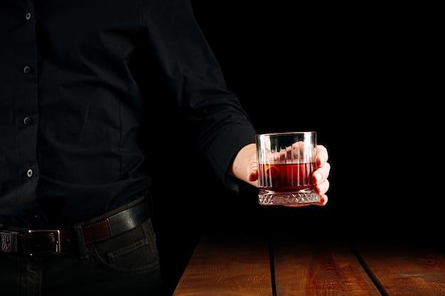 Uomo con in mano un bicchiere di negroni cocktail sopra il tavolo di legno