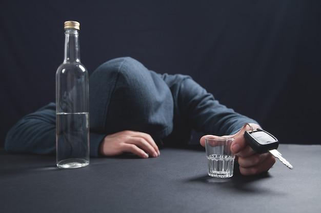 Uomo con un bicchiere di vodka e chiave dell'auto.