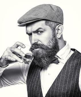 Uomo con in mano un bicchiere di whisky. ritratto di uomo con barba folta. degustazione, degustazione. sorseggiando whisky. bere da macho. l'uomo con la barba tiene il brandy di vetro. bevanda barbuta cognac. bianco e nero.